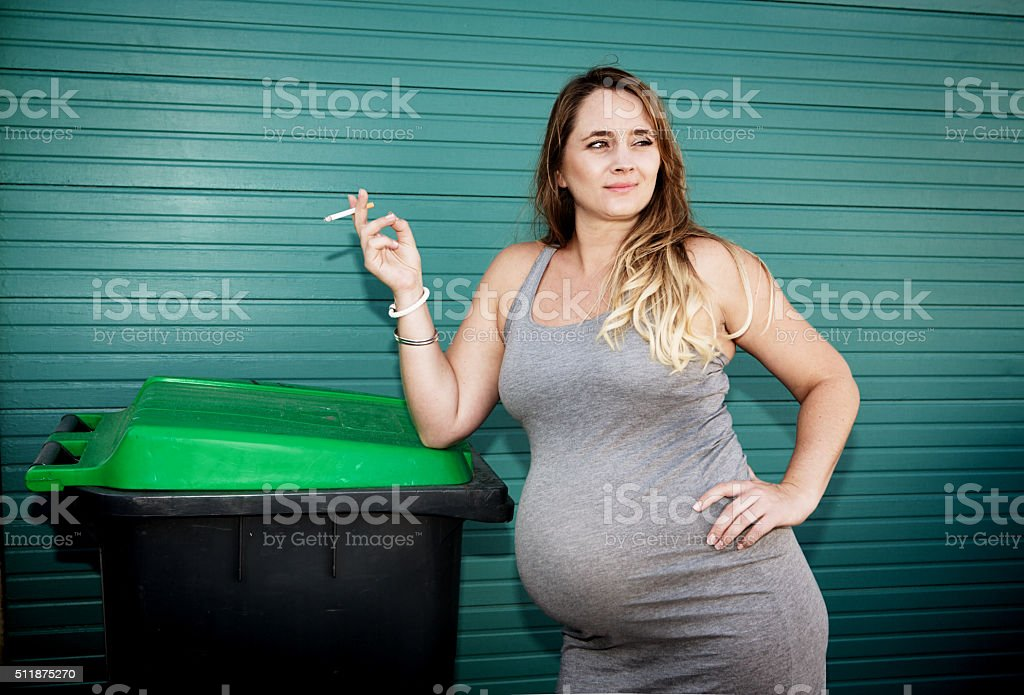 Bad habits: very pregnant woman smoking a cigarette stock photo