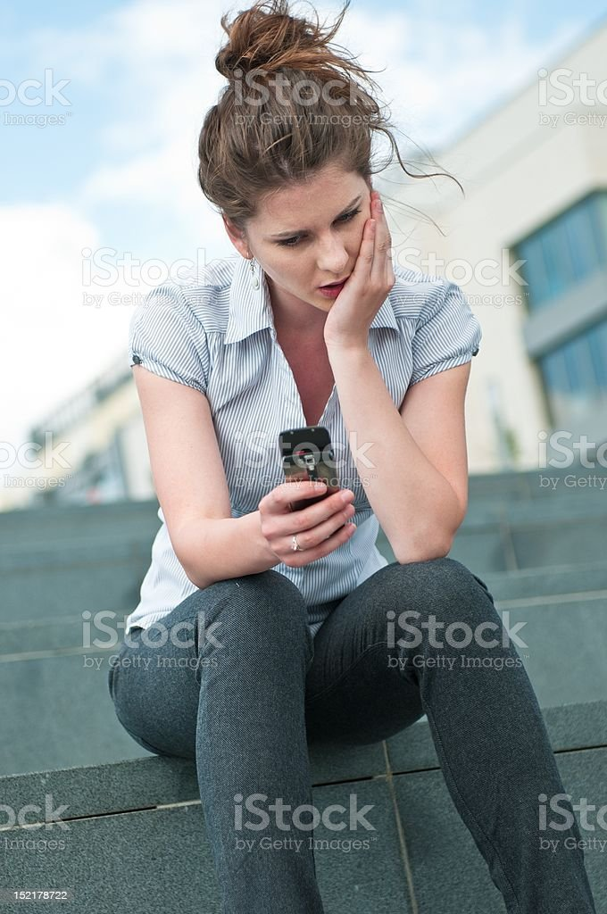 Bad message - unhappy woman with mobile phone royalty-free stock photo