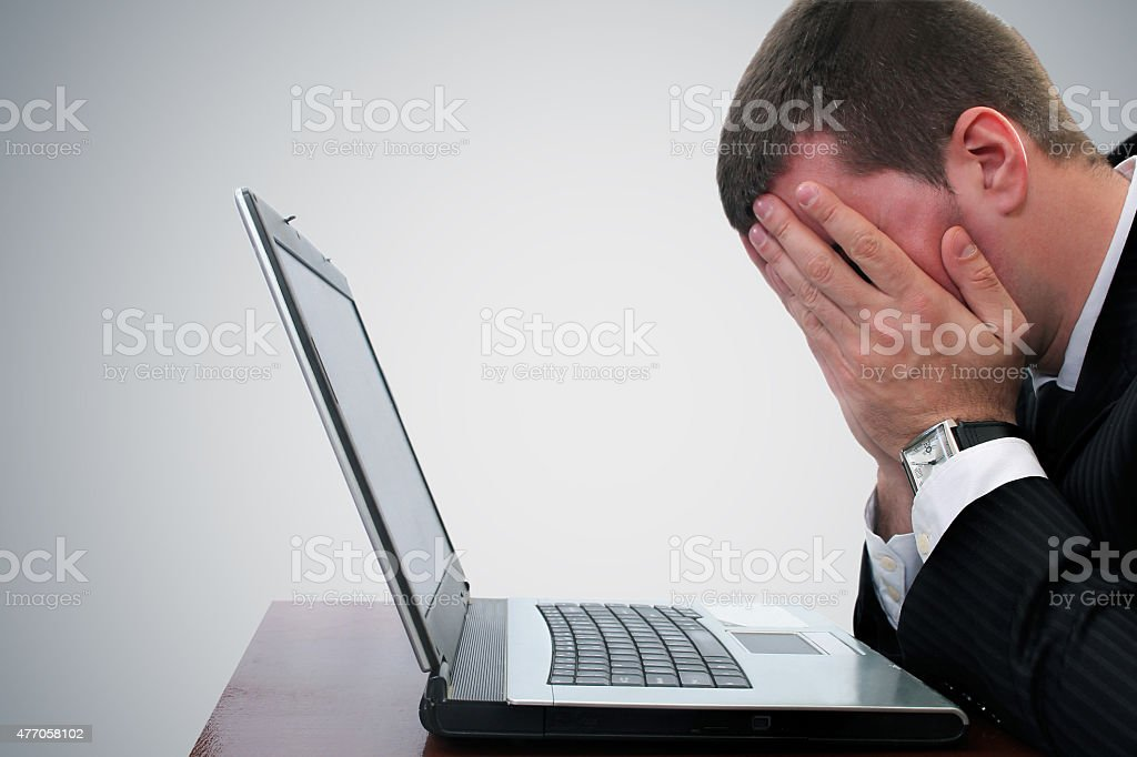 Bad News Businessman Shielding Eyes at Desk stock photo