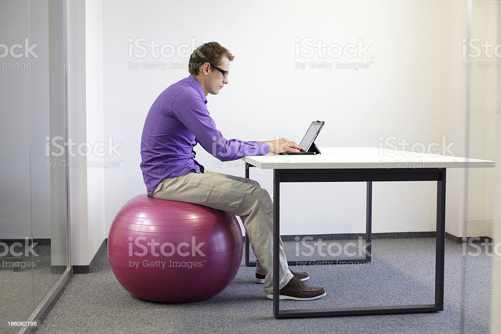 bad sitting posture at tablet on stability ball stock photo