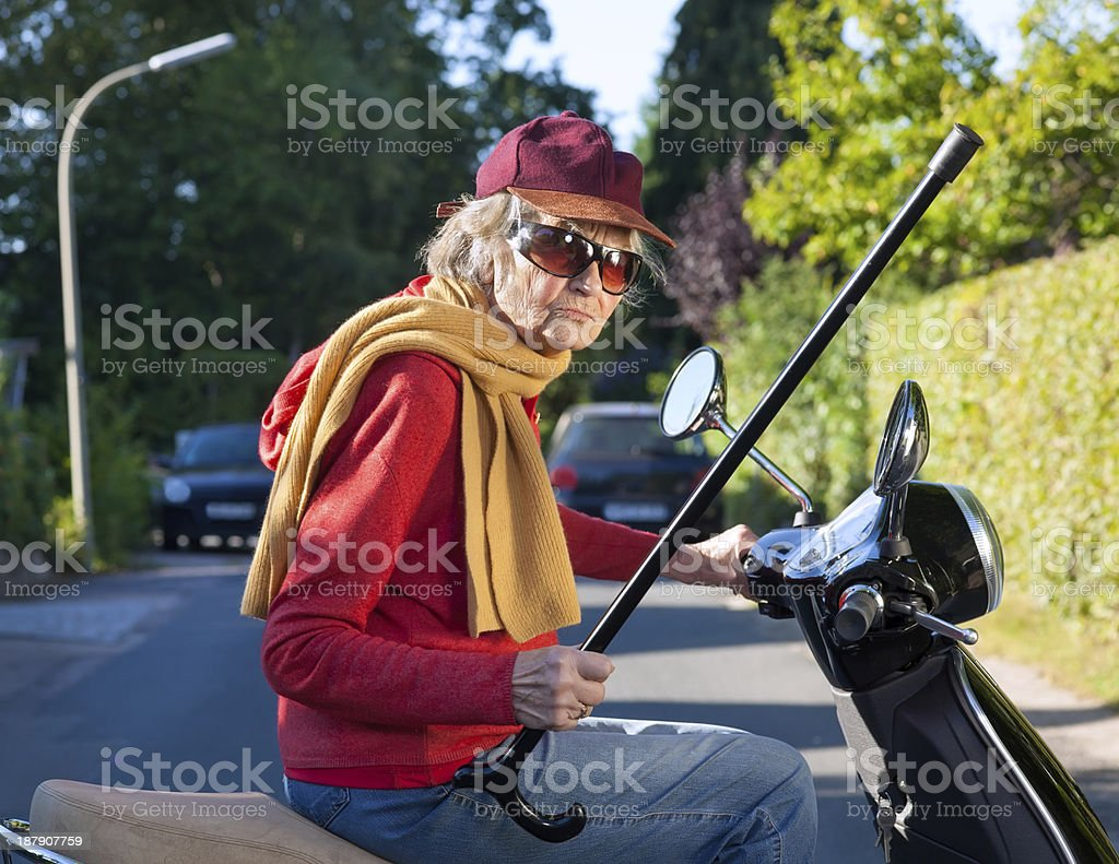 Bad tempered old woman with a walking stick. stock photo