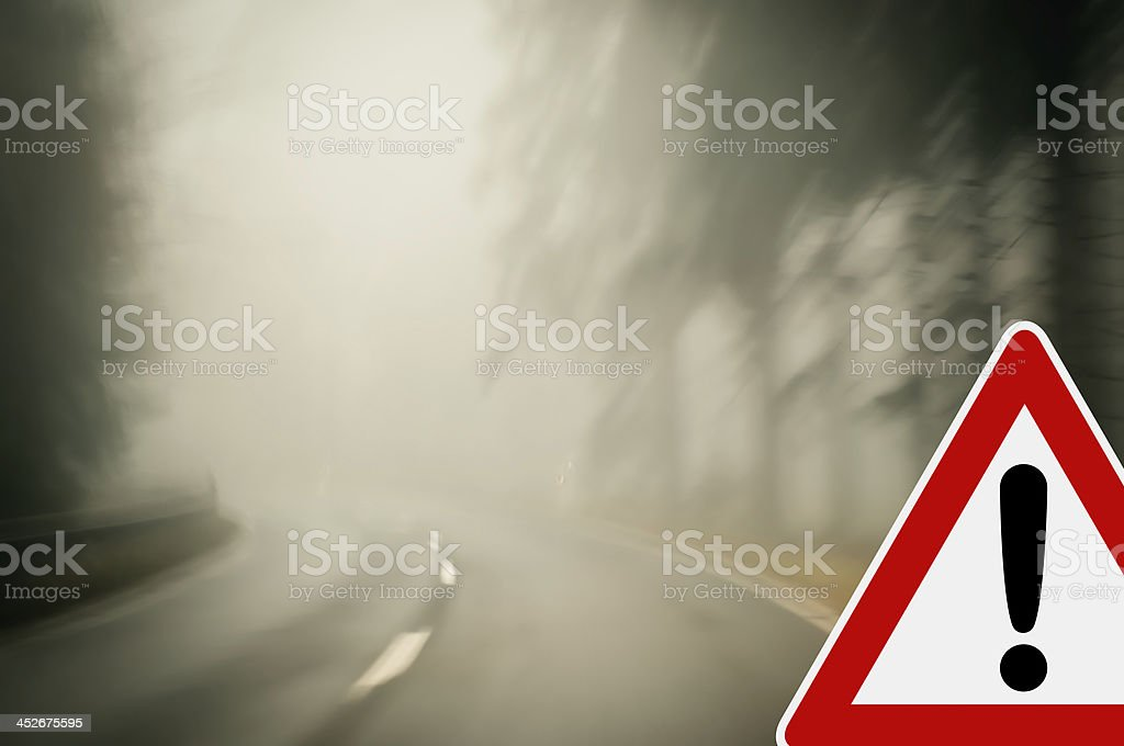 Bad weather driving - foggy road with traffic sign stock photo
