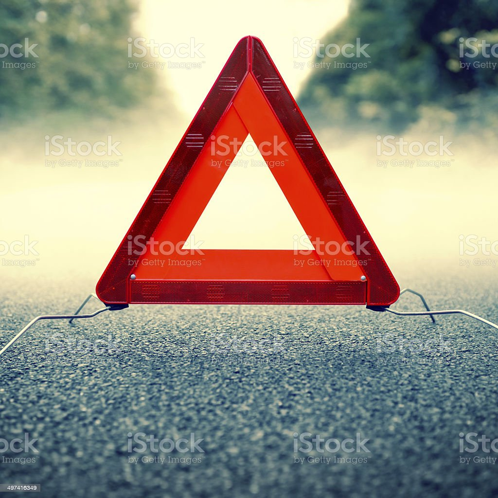 Bad weather driving - warning triangle on a foggy road stock photo
