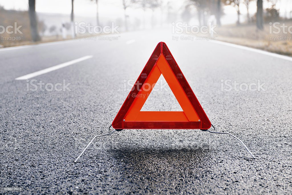 Bad Weather Driving - Warning Triangle on a Misty Road stock photo