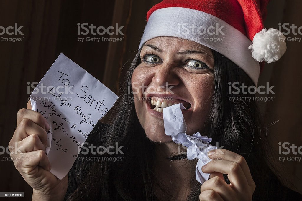 Bad Woman with Santa Hat destroying a Letter royalty-free stock photo