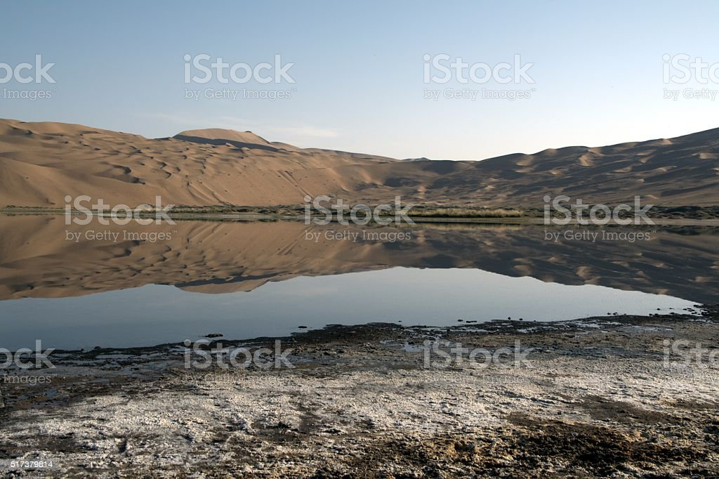 Badain Jaran desert, dune reflecting on lake, Inner Mongolia, China stock photo