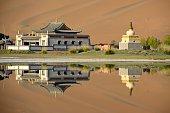 Badain Jaran Temple, reflecting on its lake, Inner Mongolia