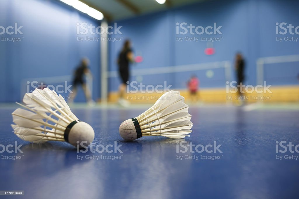 badminton courts with players competing; shuttlecocks in the foreground stock photo