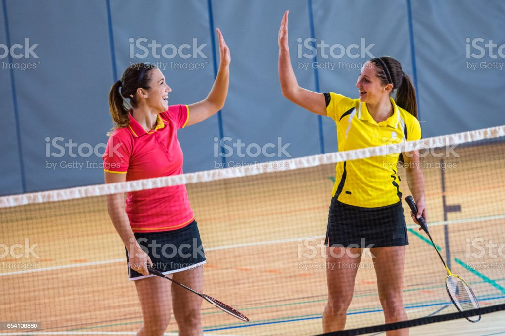 Badminton players giving high-five stock photo