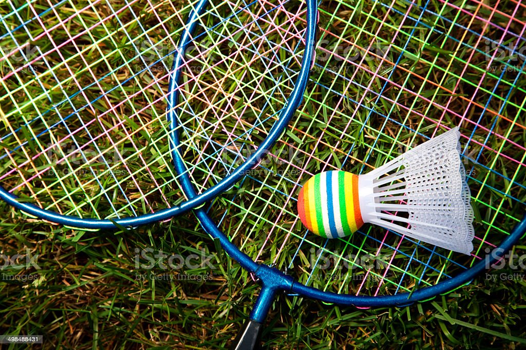 Badminton rackets and game cock on grass stock photo
