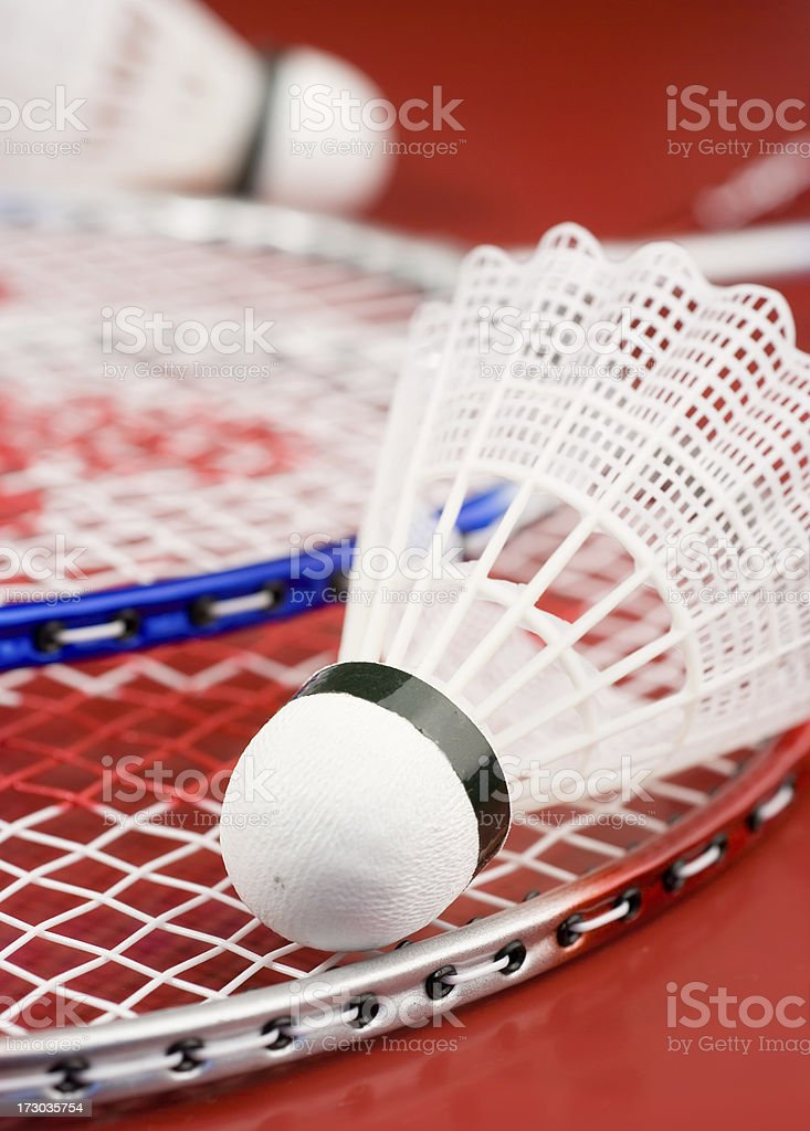 Badminton shuttlecock on red racquet on red surface stock photo