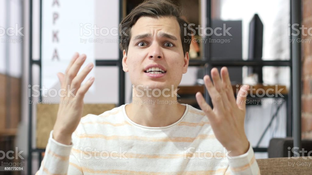 bad-tempered caucasian young man yelling on his Team stock photo