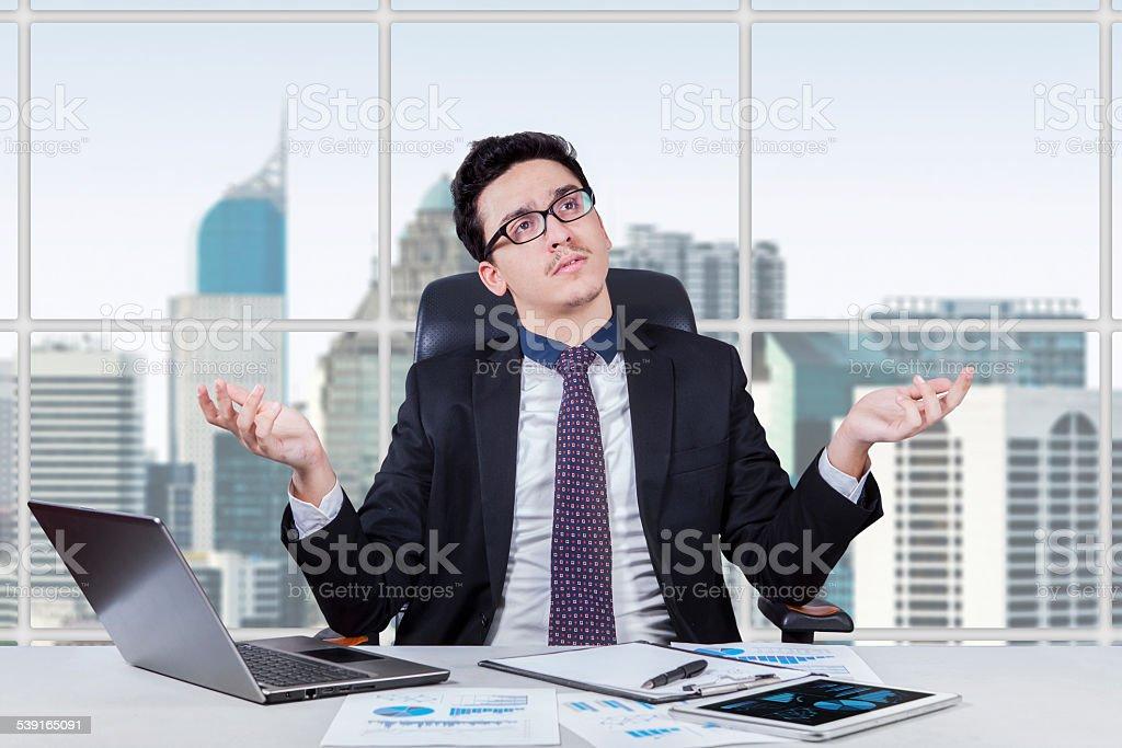 Baffled businessman finding an idea stock photo