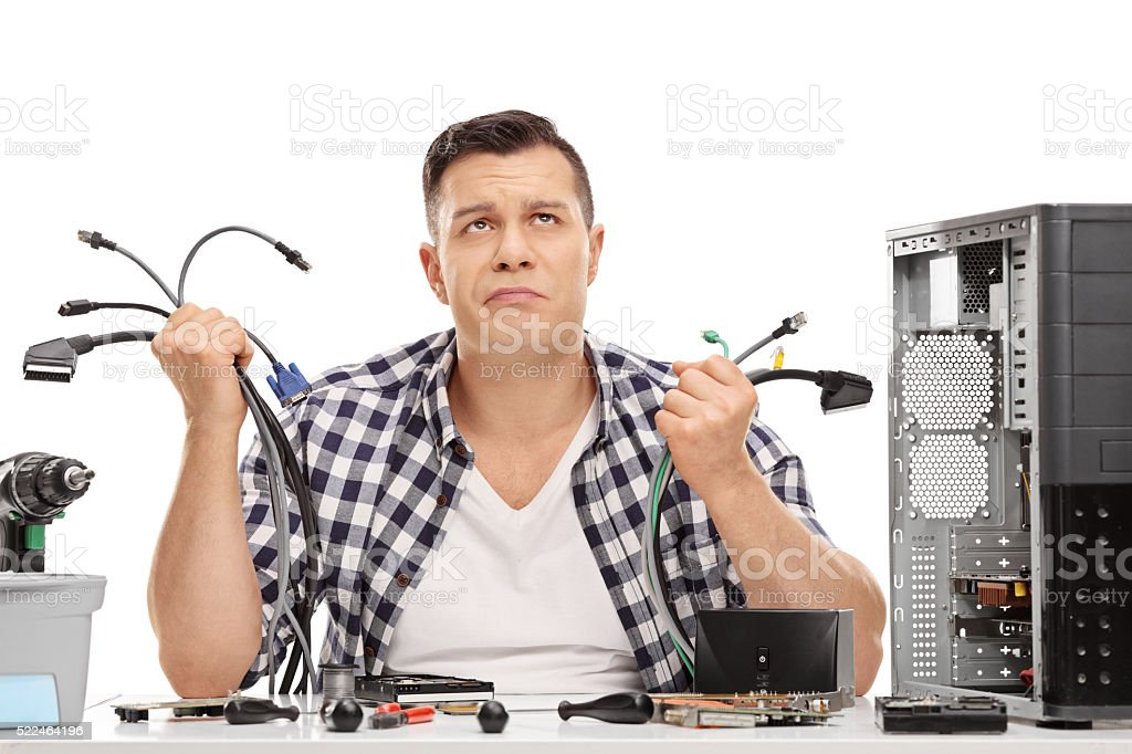 Baffled guy holding bunch of computer wires stock photo