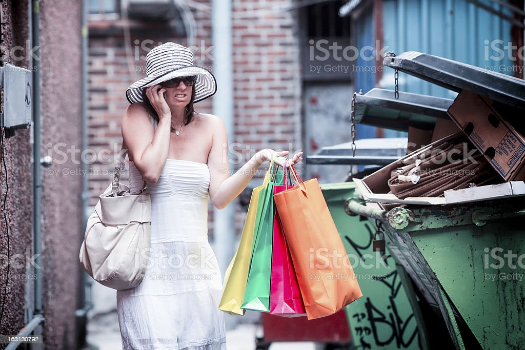 Baffled lost shopper calls for help near garbage bins stock photo
