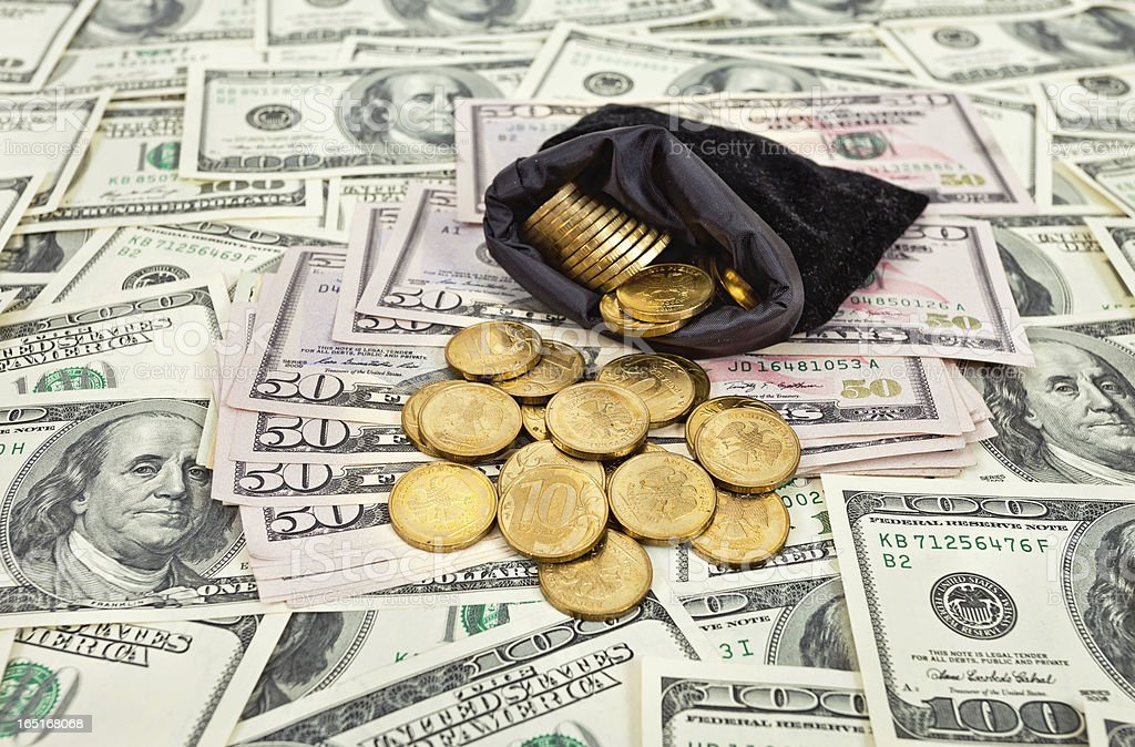 Bag filled with coins over US banknotes background royalty-free stock photo