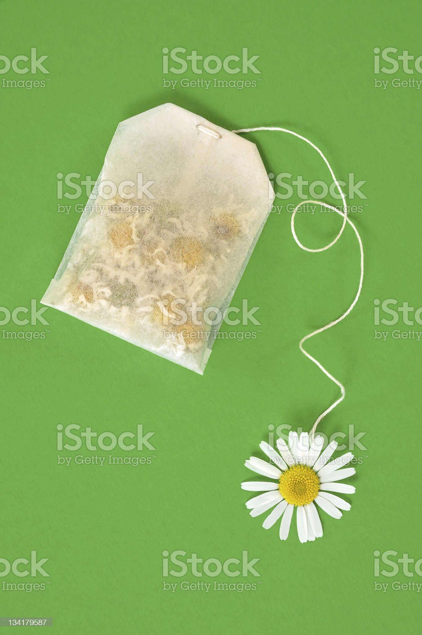 Bag of chamomile tea over green background - concept royalty-free stock photo