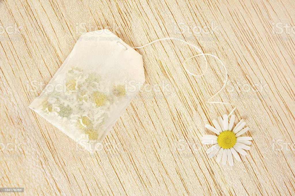 Bag of chamomile tea over wooden background - concept royalty-free stock photo