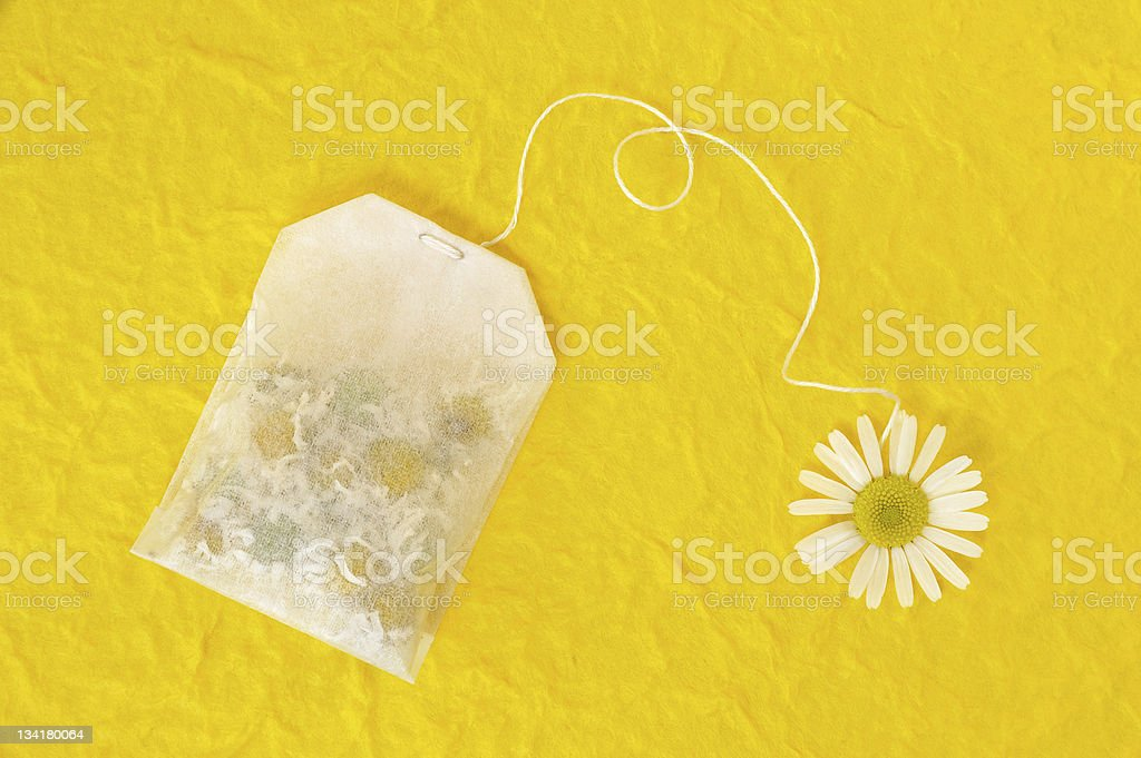 Bag of chamomile tea over yellow handmade paper - concept royalty-free stock photo