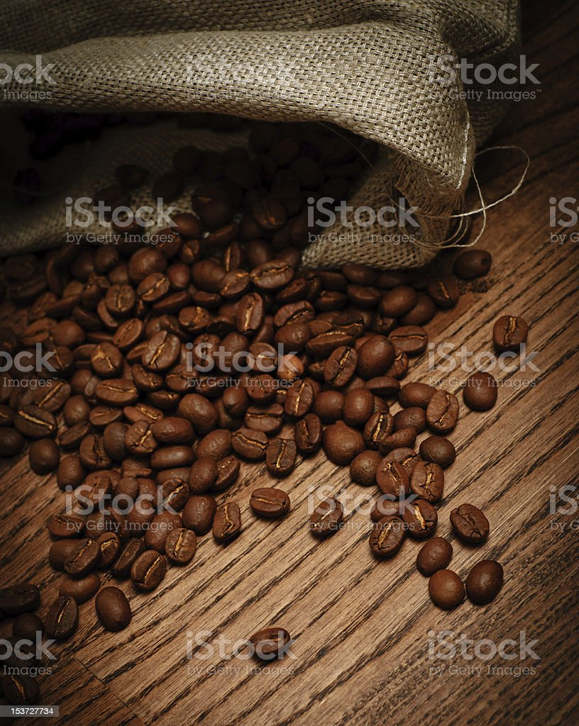 bag of coffee beans scattered on the table royalty-free stock photo