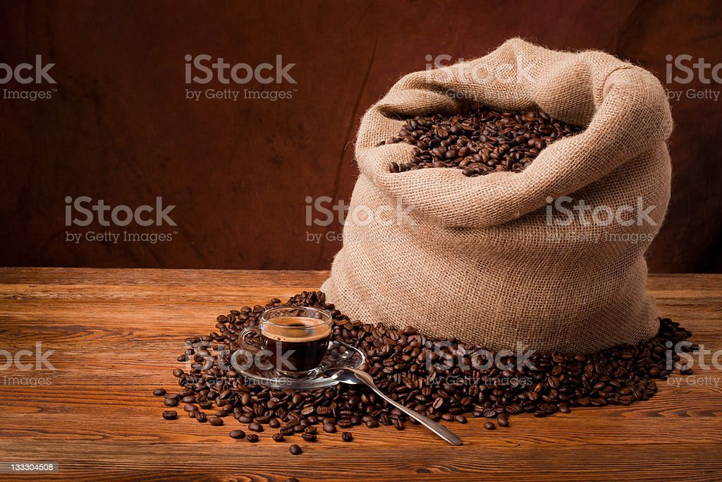 A bag of coffee beans with some spilled on a table royalty-free stock photo