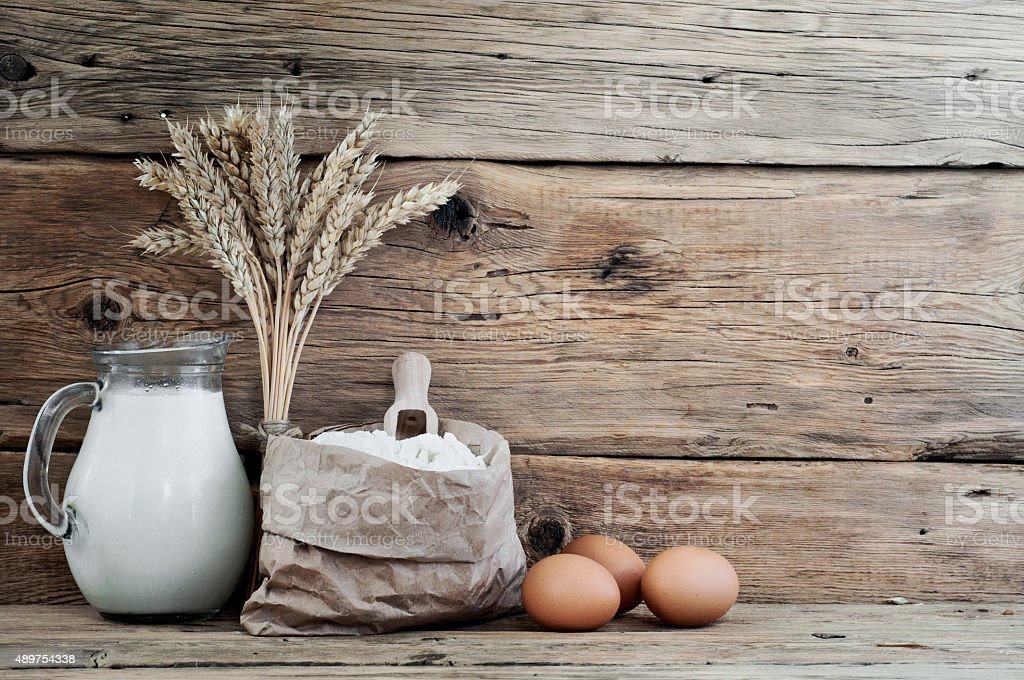 bag of flour with spikelets of wheat, milk and eggs stock photo