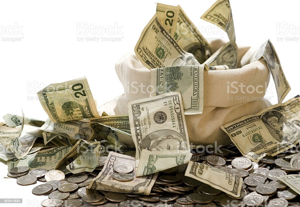 Bag of money with dollars and coins strewn about royalty-free stock photo