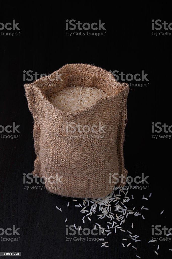 Bag of rice on black background. stock photo