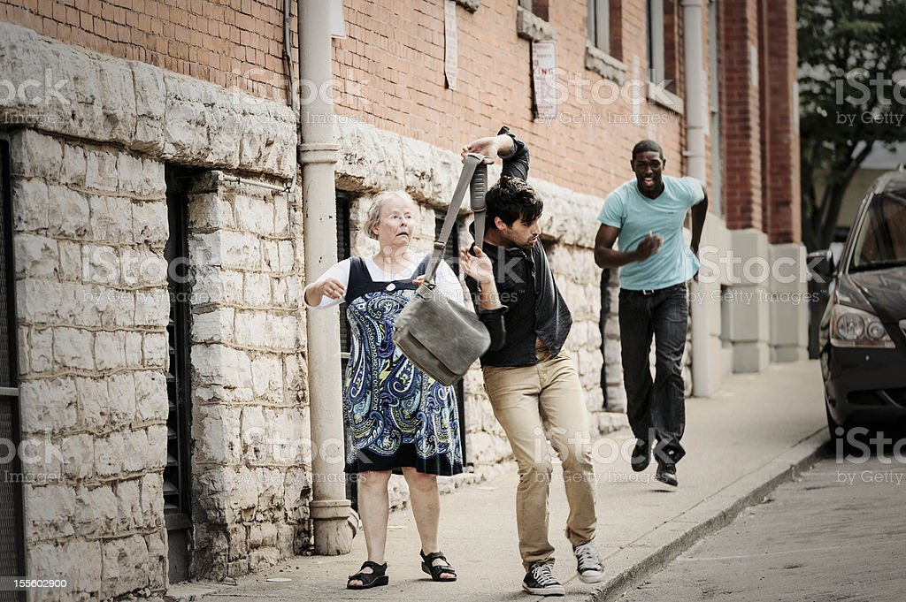 Bag Snatcher Stealing From A Senior Woman royalty-free stock photo
