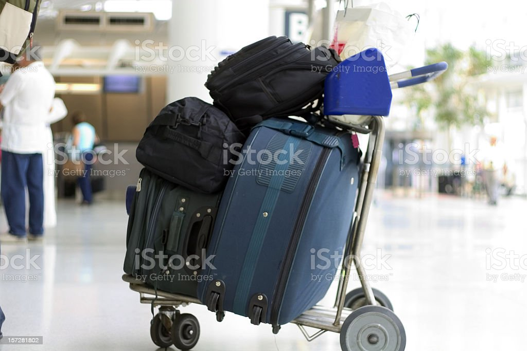 Baggage cart with bags packed on top stock photo