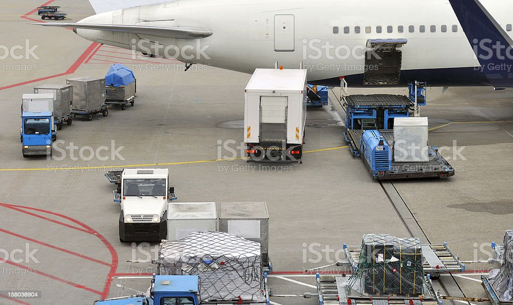 Baggage carts and food truck loading a jet airplane stock photo