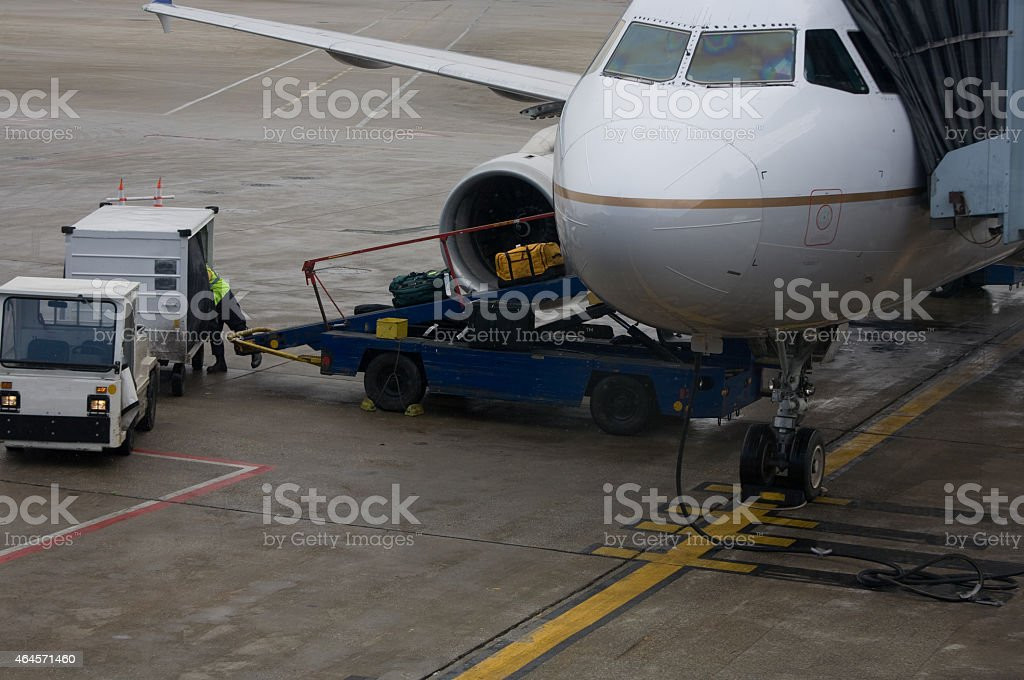 Baggage handler  loading luggage onto plane stock photo