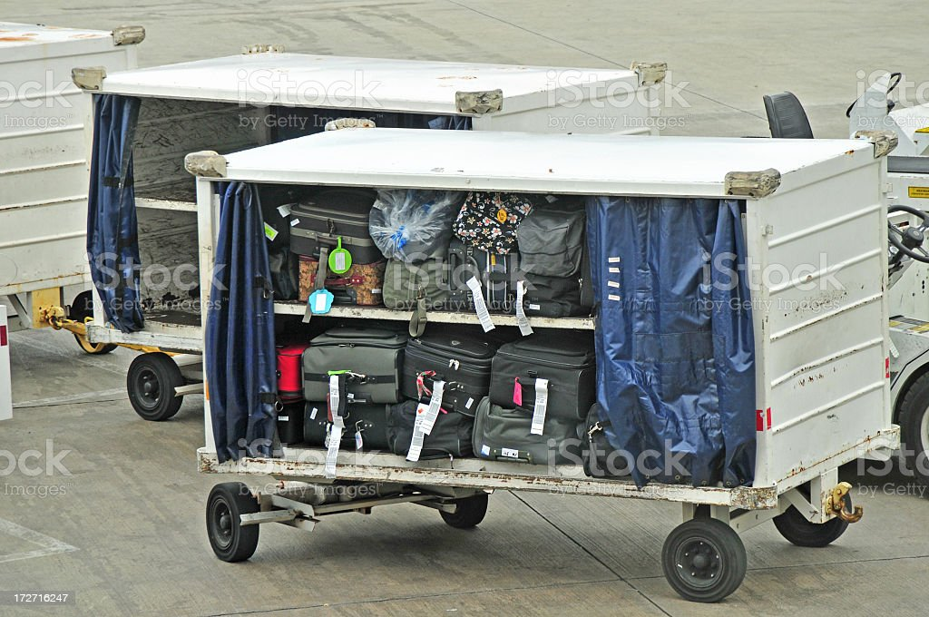 Baggage trucks at airport carrying suitcases stock photo