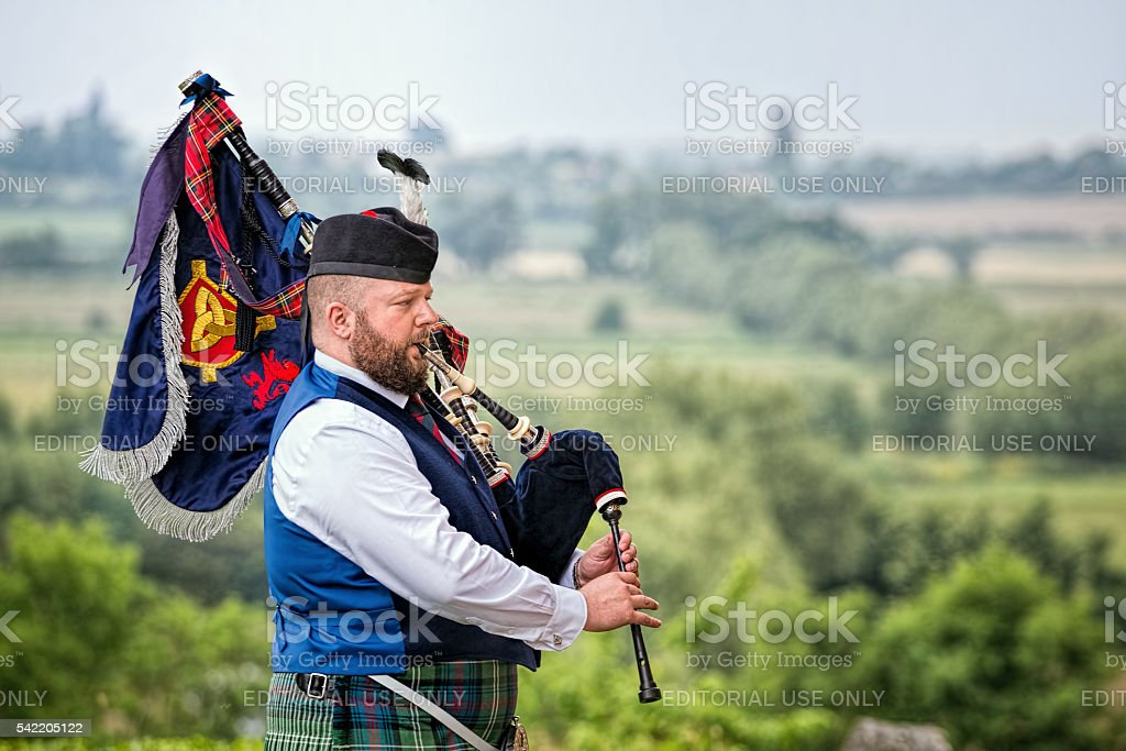Bagpiper plays bagpipes overlooking landscape. stock photo