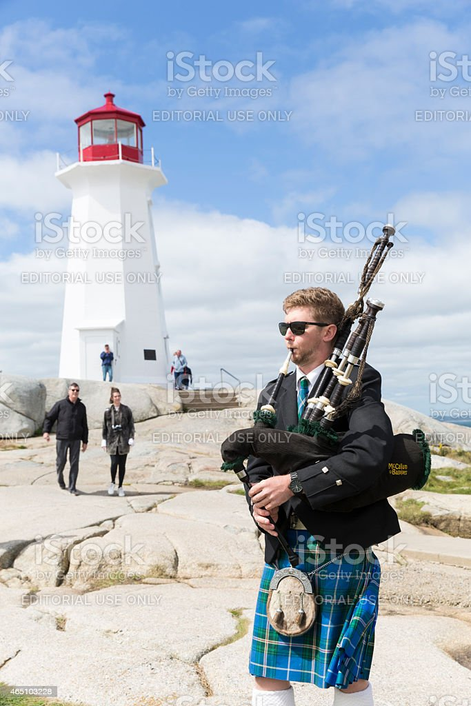 Bagpiper Plays His Bagpipes by Peggy's Cove Lighthouse stock photo