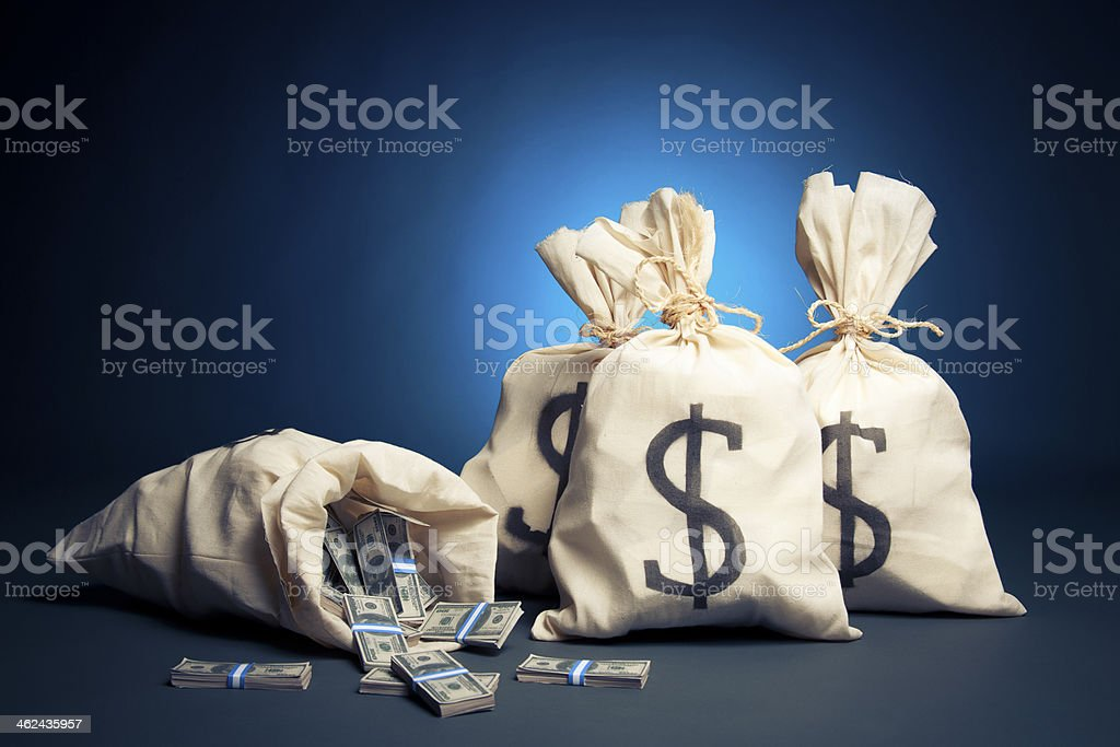 Bags full of money, dollar bills spilling out stock photo