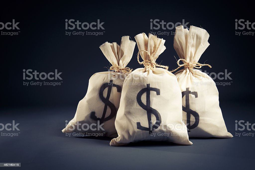 Bags full of money on a dark background stock photo