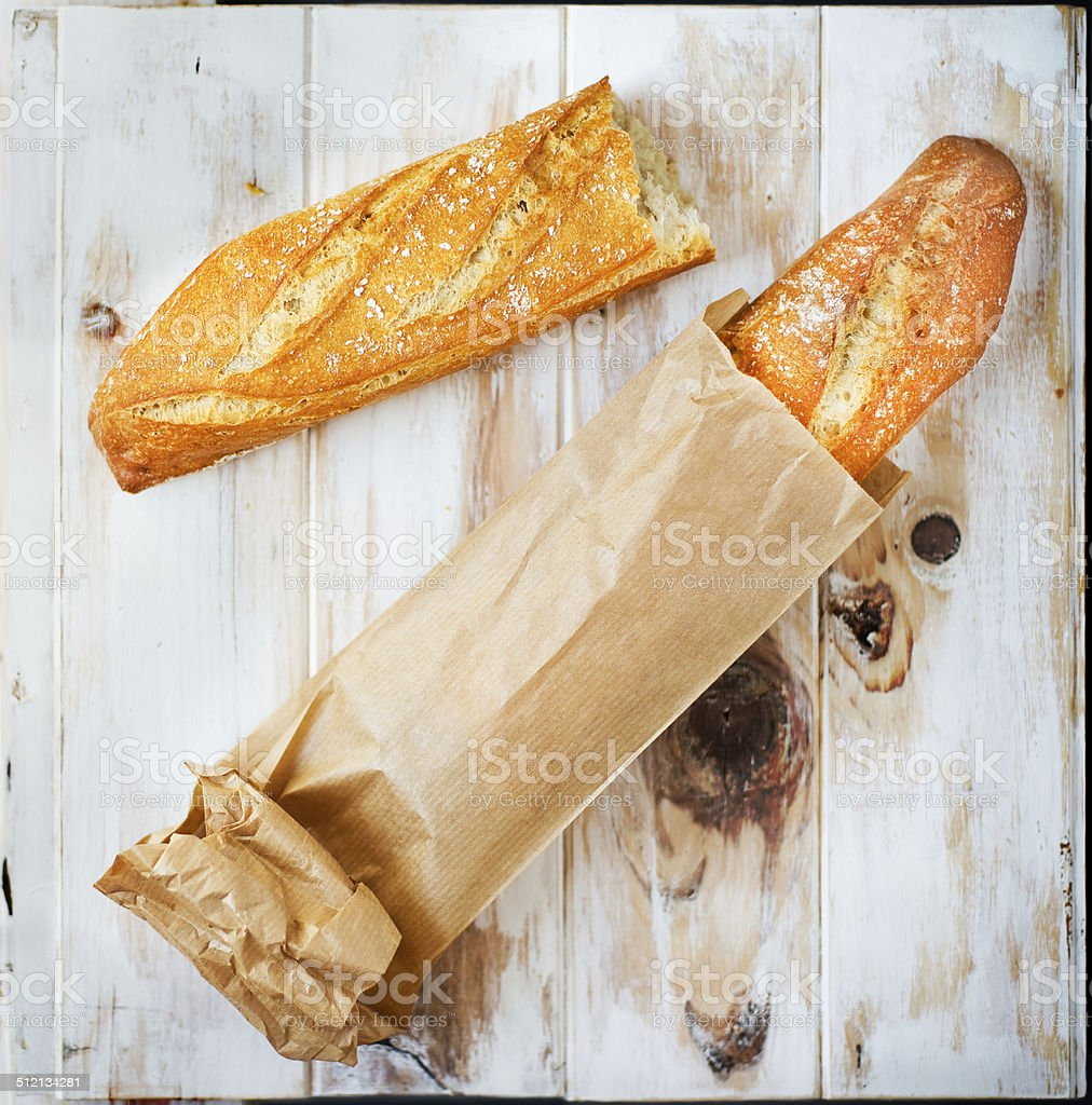 Baguette in a grocey paper bag. Loaf of bread stock photo