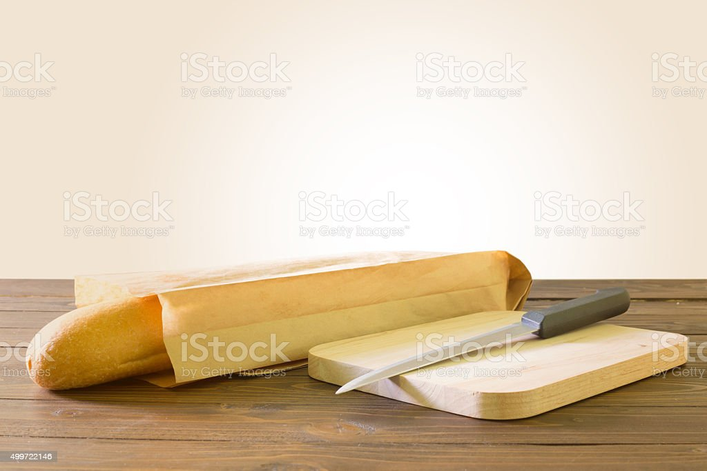 Baguette in paper container with knif on wooden table stock photo