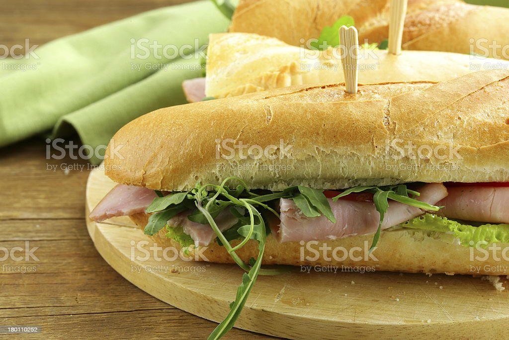 baguette sandwich with arugula, ham and tomatoes royalty-free stock photo