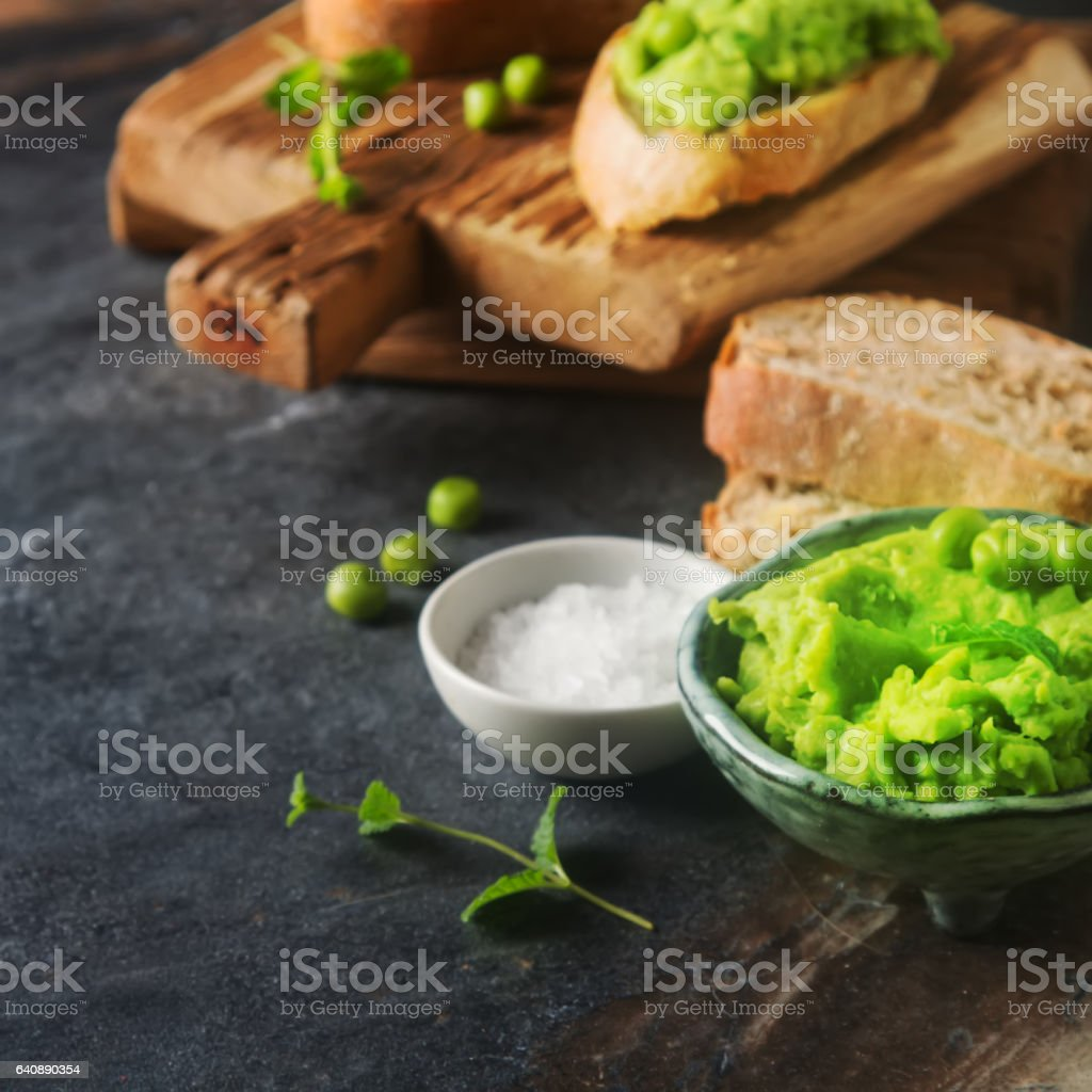 Baguette with mashed green peas and mint. Dark background. Selec stock photo