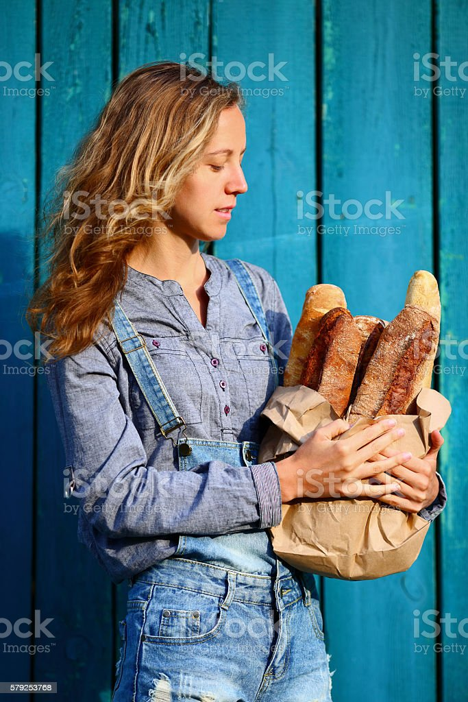 Baguette. Woman is holding in hands a bag with baguettes stock photo