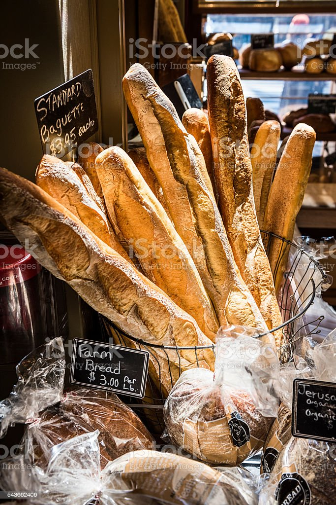 Baguettes by a windowsill in a bakery with sunlight stock photo