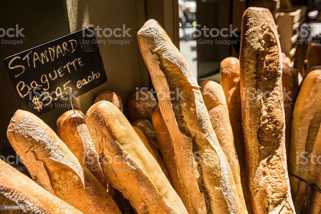 Baguettes in early morning sunlight by a windowsill stock photo