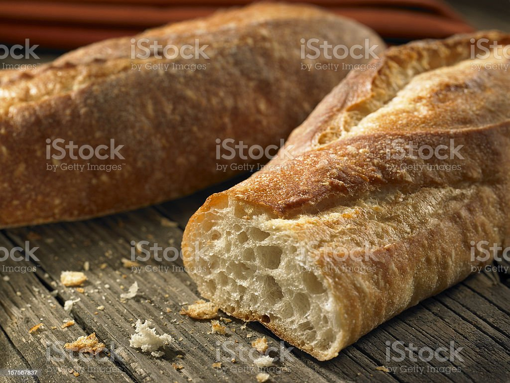 Baguettes with crumbs on weathered background stock photo