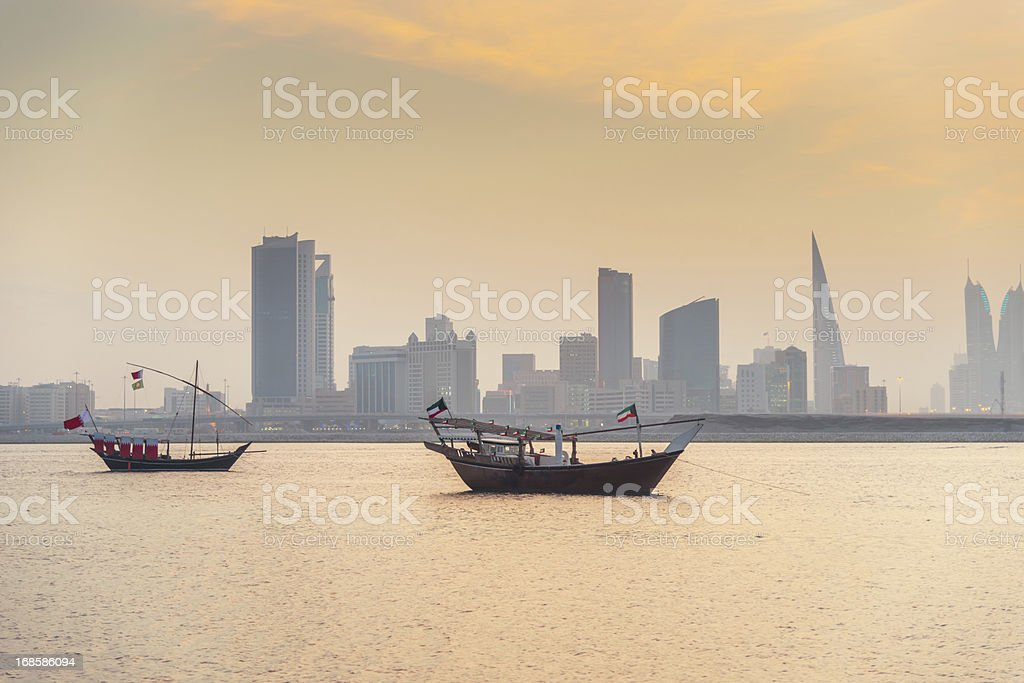 Bahrain Manama Skyline and Dhows at Sunset stock photo