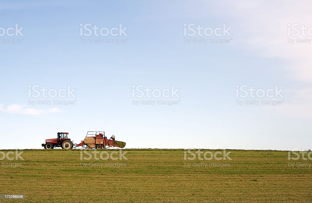 Bailing hay in a field with tractor stock photo