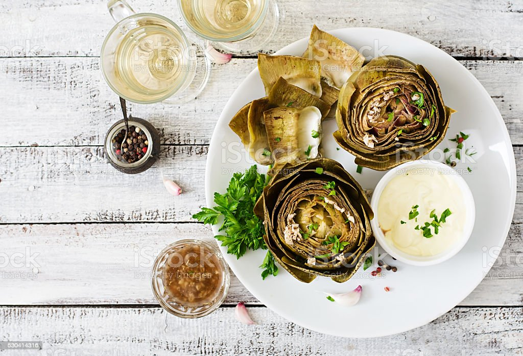 Baked artichokes cooked with garlic sauce, mustard and parsley stock photo