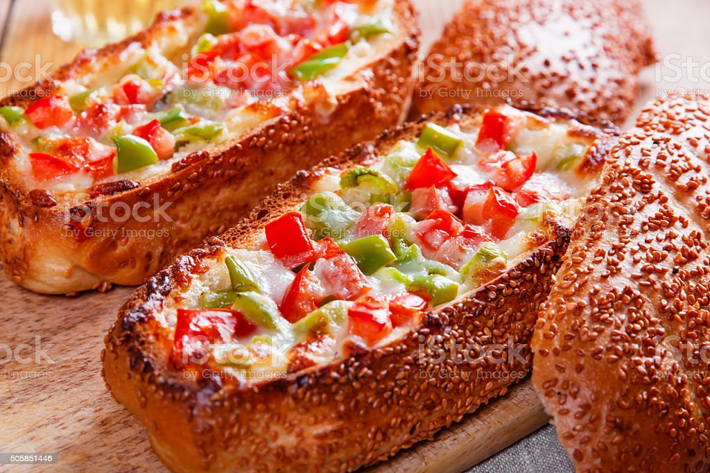 baked baguette stuffed with vegetables and cheese stock photo