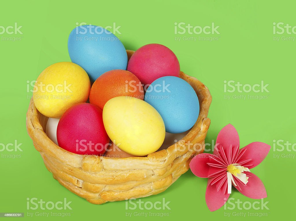 Baked basket with Easter colored eggs on a green background royalty-free stock photo